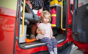 Emmy, 2,5 år provsatt brandbilen. Här är hon på väg ut ur räddningstjänstens fordon.