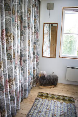 Förvaring är en utmaning i det lilla huset där den klädkammare som fanns gjorts om till badrum. Här har en garderob gömts bakom vackra draperier i sovrummet.