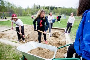 Fyrtio föräldrar och lika många barn hjälper till med uppfräschandet av skolgården.