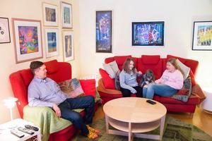Stefan, Ellen, hunden Morris och Edith pustar ut i den röda soffgruppen i familjen Gavells lägenhet.