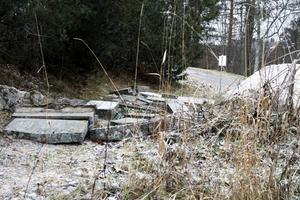 Gravstenarna har lyfts upp från gravplatser och lagts ner på marken på en plats bredvid den nyare delen av kyrkogården i Enånger.
