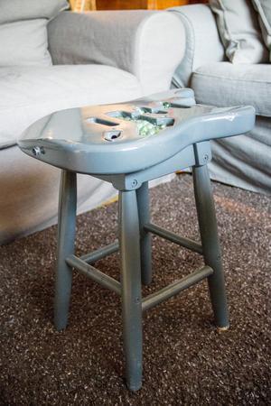 En trasig elgitarr som gjorts om till pall eller litet bord, med glaskulor som dekoration i hålrummen.