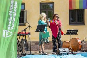 Liselotte Fluhr ger Ann-Helen Persson regnbågsfärgade strumpor som tack för det jobb hon gör.