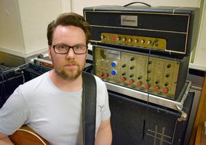 Henric bredvid en av sina gitarrförstärkare.