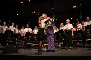 Per-Olof Ukkonen tar emot blommor från orkestern, här representerad av Marie Fröjd.