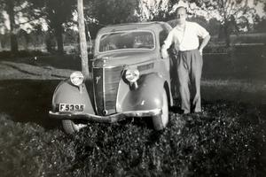 En stolt Sven-Eric Svensson med sin allra första bil. Fotot är lite skadat men bilen ståtar i all sin prakt. Foto: Privat