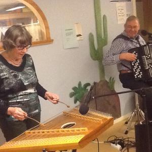 Karin och Åke på Torsvik. Karin spelar på ett unikt instrument. En hackbräda av cittratyp, i samband med österrikisk och annan central- östeuropeisk musik känt som cembalon (även zimbalon och cymbal). Åke på dragspelet.