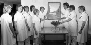 1983 fick sjukhuset i Svenstavik en gåva av målaren Jöns Anton Andersson, Bergsviken. Den då 100-årige konstnären vårdades på avdelning 2 under sin sista tid och skänkte den sista tavlan han målade till sjukhuset. På bilden provhänger Heidi Larsson och Rolf Karlsson tavlan under överinseende av övrig personal på avdelning 2.