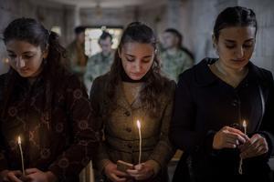 Kvinnor tänder ljus, med amerikanska soldater i bakgrunden, under en julmässa i den ortodoxa kyrkan Mar Shmoni i Bartella i Irak. Foto: Cengiz Yar/AP Photo
