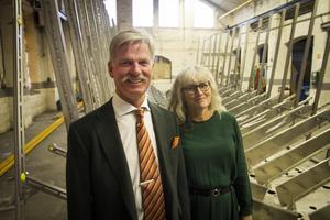Håkan och Petra Rosén i verkstaden som saknar arbetare i nuläget. På den bortre gaveln ska tavlan hänga.