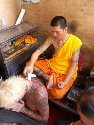 Välsignad. Jocke har själv en och annan tatuering på sin kropp. Här blir en ny tatuering välsignad av en thailändsk buddist-munk.