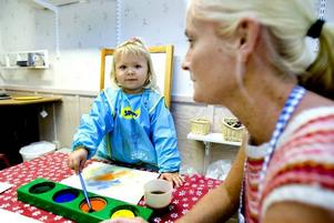 """gillar pyssel. Patricia Åkerberg, tre år, trivs redan bra på nya Smultronet. Framförallt gillar hon pysselrummet. """"För det är roligt att måla"""", säger hon. Även fröken Madelene Svenneke uppskattar de nya fräscha lokalerna på Marstrandsvägen."""