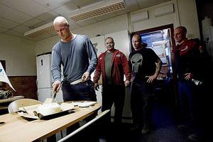 Tomas Blom skär första biten i jubileumstårtan. Arbetskamraterna Mikael Eriksson, Robert Knief och Patrik Göransson väntar på sin tur.