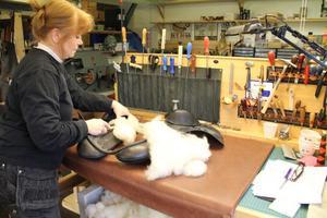 Ett vanligt uppdrag i sadelmakeriet är att stoppa om gamla sadlar med ren ull. Här jobbar Siw med en engelsk sadel. Hon matar in ullen.