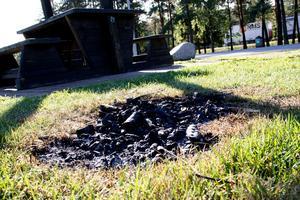 Vid Svedvi rastplats har någon gjort upp en eld på gräsmattan.