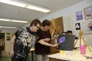 Tipsar. Eila Lindblom, Skinnskatteberg, ger tips och idéer till sina målarkollegor. Här instruerar Eila sin tvillingsyster Eva Korhonen.
