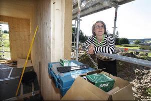 Monika Roos tittar in genom fönstret på nya huset. Här syns hur tjocka väggarna är och ännu tjockare blir de när ytterpanelen är på plats.
