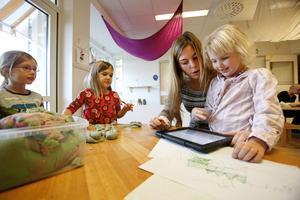Miranda Bergman Linder och Ellen Grape tittar när Sofie Skärberg hjälper Clara Graflind med hennes bok.