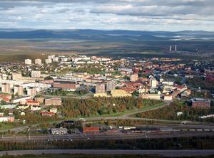 Kiruna sett från Kiirunavaara, berget där LKAB:s gruva finns. Närmast syns järnvägsstationen, som nu är riven,  och centrum och en stor del av de bostäder som måste bort. Nya centrum och de flesta nya bostäderna byggs vid de två tornen längst bak på bilden, vid Tuolluvaara. Tornen är rester av en nedlagd gruva.