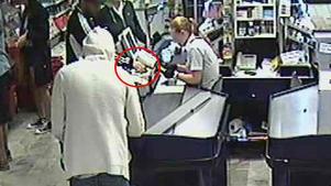 De två männen, i svart och grå munkjacka, löser här in lotter på en butik. Åklagare hävdar att männen stulit 700 trisslotter.