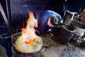 Varmt. Sören Gustavsson har just dragit i gång smältugnen. Det kan bli uppemot 1700 grader i ugnen. Bronsets gjuttemperatur ligger runt 1250 till 1300 grader.