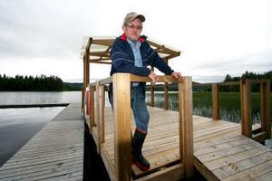 Lars Karlström, ordförande i Bredsjöns/Slättmons byalag står på flotten som är ligger intill bryggan nere vid badplatsen. — Det fattas bänkar och en motor, innan flotten är helt färdig, säger han.
