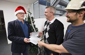 Julklappsudelning på Nordikon. Mikael Kölborg, delägare i företaget, delar ut julklappar till platschefen Stefan Kjellbo och snickaren Björn Källstrand.