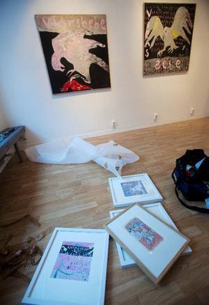 Hängning pågår.  På väggen olje-målningar  av Camilla Pyk.  På golvet några  av faster Madeleines mindre tavlor  i akvarell och gouache.Foto: Håkan Luthman