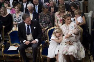 Christopher O'Neill och prinsessan Madeleine med Nicholas (i bakgrunden) och Leonore under dopgudstjänsten för prinsessan Adrienne Josephine Alice i Drottningholms slottskyrka. Barnen kommer inte längre att tituleras