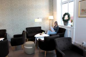 Lärarvikarien Julia Östling Kütt tar en paus i personalrummet med guldbeige medaljongtapet och bruna möbler.