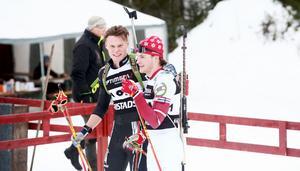 Henning Sjökvist klappar om Malte Stefansson efter målgång i jaktstarten i Swecup-tävlingarna i skidskytte i Lima.