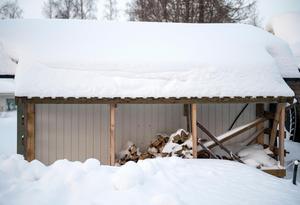 Under tak längs med ett uthus på tomten ligger björkveden staplad.