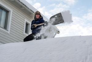 Cija Westberg skottar snö från garagetaket. Bilden tagen vintern 2018.