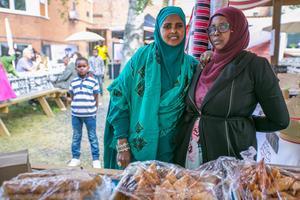 Torvallakvinnorna Zahra Hassan Mohamed till vänster och Halimo Mahamed Osman serverade mat från hemlandet Somalia. Bakom dem Halimos 6-årige granne Abdiraxmaan Idi.