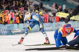 En trött Stina Nilsson går i mål samtidigt som Norge jublar efter OS-guldet i förgrunden. Bild: Joel Marklund/Bildbyrån.