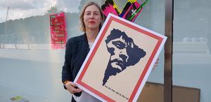 Nina Beckmann är chef för Grafikens hus. Här med en affisch av Olof sandahl. I bakgrunden affischer av Parasto Backman.