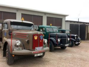OVe Thomsons lastbilar uppradade framför garaget, närmast kameran en Scania från 1957, sedan en Volvo från 1952 och slutligen ytterligare en Volvo men denna av årsmodell 1935.