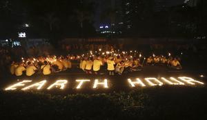 Med tända ljus agerar aktivister för att rädda klimatet. Foto: Tatan Syuflana/TT