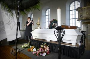 Hon dokumenterar under begravningen för att ge de anhöriga ett personligt fotoalbum.