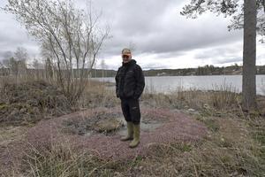 Lasse Matsson Liden vid avloppsbrunnen som fått en grusbädd runt sig. Hela bädden var nyligen översvämmad av avloppsvatten.