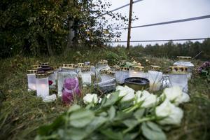 Många ljus och blommor ligger vid olycksplatsen i Pusselbo.