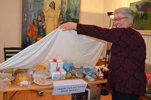 Lena Persson lyfter bort täckelsen och bjuder in hågade spekulanter till försäljningsbordet.