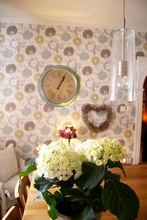 Blommor både på bordet och väggen i köket.