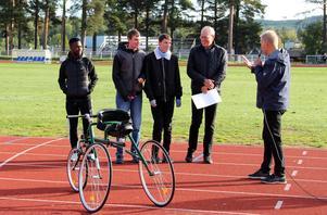 En check på 10 000 kronor till Parasportförbundet Dalarna, för anskaffning av en racerunning-cykel. Adam och Daniel Hansson delar ut checken, som kommer från deras stiftelse. Pappa Anders Hansson håller i checken. Maslah Omar, kultur - och fritidsnämndens ordförande och Ola Brossberg, ordförande i Dalarnas Parasportförbund.