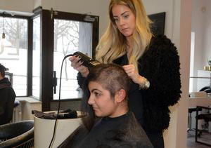 Frisören Malin Björn på Salong Luxe i Sundsvall avlägsnar Asals hår.