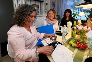 Ulrica Falk bläddrar bland gamla minnen i form av bland annat recept och inbjudningar. Berit Engberg och Lena Ödlund hjälper till att minnas
