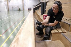 Peter Gustafsson från företaget Golv1 lägger på lim för att fästa en matta vid läktarens sarg.