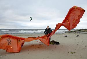 Urban Lind pumpar upp drakens framkant med luft för att få bättre vingprofil på kiten.
