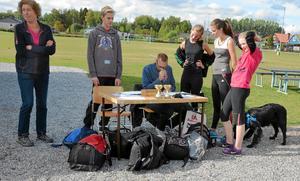 Kollar tiderna. Tider och kontrollstämplar måste räknas samman för orienterarna och eleverna vill gärna se tabellen som Rickard Eriksson har på bordet.