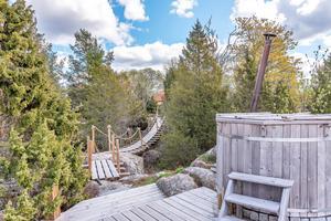På tomten finns en rustik gångbro, som mer liknar en vallgrav, över till en badtunna.  Foto: Fisheye Foto i Roslagen